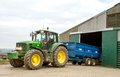 Modern John Deere tractor parking blue trailer Royalty Free Stock Photo