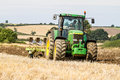 Modern John Deere tractor pulling a plough