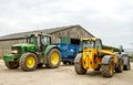 Modern john deere tractor and trailer parked with jcb loader blue agri loadall in farm yard barn Royalty Free Stock Photos