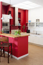 Modern kitchen interior with bar red walls and white furniture and at the foreground Royalty Free Stock Photography