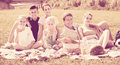 Modern large family of six having picnic on green lawn in park Royalty Free Stock Photo