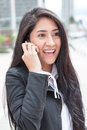 Modern latin woman with phone in the city Royalty Free Stock Photo