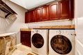 Modern laundry room with cabinets and granite top interior whtie appliances bright wooden tops Stock Image