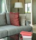 Modern living room design with red pillows on sofa and lamp Royalty Free Stock Photo