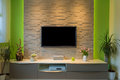 Modern living room interior - tv mounted on brick wall with black screen and ambient light Royalty Free Stock Photo