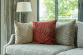 Modern living room with red pillows on gray sofa and decorative lamp at home Royalty Free Stock Photo