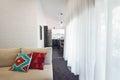 Modern living room sofa and sheer curtains horizontal cushions Royalty Free Stock Image