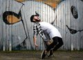 Modern male dancer portrait of a with beard posing against graffiti wall outdoors Stock Photo