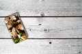 Modern mobile device showing mussels on top of an old wooden table Stock Photos