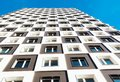 Modern and new apartment building. Photo of a tall block of flats with balconies against a blue sky. Royalty Free Stock Photo