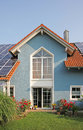 Modern new built house and garden rooftop with solar cells blue front lattice window Royalty Free Stock Photo