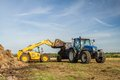 Modern new holland tractor tractor being loaded up with muck for muck spreading a blue to manure on fields land muckspreading by Royalty Free Stock Image