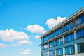 Modern office building against blue cloudy sky Royalty Free Stock Photo