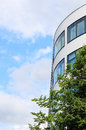 Modern office building with mirrored windows and tree against blue sky as background copy space free place for text Stock Photography