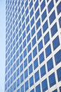 Modern office building reflecting blue sky in many square windows Stock Photos