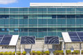 Modern office with solar power ground level panel arrays in front of building Stock Photo