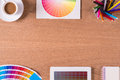Modern office workplace with digital tablet, notepad, colorful pencils, cup of coffee, and color swatches on a desktop Royalty Free Stock Photo