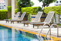 Modern pool with deck chairs Royalty Free Stock Photo
