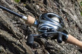 Modern powerful fishing reel spinning close up on a tree trunk Stock Photos