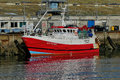 Modern Red Fishing boat alongside the wharf. Royalty Free Stock Photo