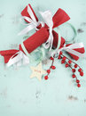 Modern red and white Christmas bon bons on aqua blue wood background. Vertical closeup. Royalty Free Stock Photo