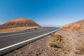 Modern road on fuerteventura by ancient volcano goes Royalty Free Stock Photography