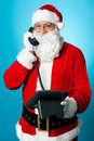 Modern Santa passing greetings over a phone call Royalty Free Stock Photos