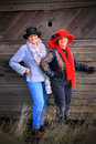 Modern sassy cowgirls two fancy cowboy ladies wearing fancy hats and dressed elegantly standing by an old barn wood wall Stock Image