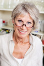 Modern senior lady in her kitchen head and shoulders portrait of an attractive smiling wearing spectacles Royalty Free Stock Photos