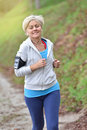 Modern senior woman jogging outdoors listening to music Royalty Free Stock Photo