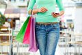 Modern shopper close up shot of a with a mobile phone and colorful shopping bags Royalty Free Stock Image