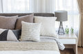 Modern style bedroom with pillows on bed and modern grey lamp on Royalty Free Stock Photo