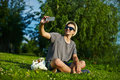 Modern stylish man in casual cloth in hat portrait of young attractive glasses sitting the park green grass making selfie Stock Photos