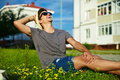 Modern stylish man in casual cloth in hat portrait of young smiling attractive sunglasses sitting the park green grass Stock Images