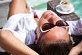 Modern and stylish relaxation young female on a vacation sunbathing with morning coffee on a recliner next to a style pool Stock Photo