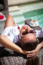 Modern and stylish relaxation young female on a vacation sunbathing with morning coffee on a recliner next to a style pool Royalty Free Stock Photography