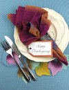 Modern thanksgiving dining table place setting with autumn leaves vertical on aqua blue tablecloth material in pink blue and Stock Image