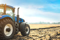 Modern tractor working in a field. Royalty Free Stock Photo