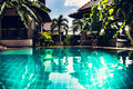 Modern tropical villa with swimming pool and palm trees Royalty Free Stock Photo