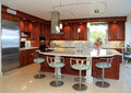 Modern upscale kitchen with marble counter and designed bar stools Stock Image