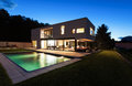 Modern villa with pool night scene Royalty Free Stock Photos