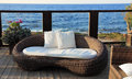 A modern wicker garden sofa in the terrace with sea view Royalty Free Stock Photography