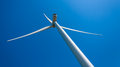 Modern wind turbine providing energy view from above and back large propeller against blue sky sunny day Stock Photo