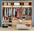 Modern wooden wardrobe with clothes hanging on rail in walk in closet design interior Royalty Free Stock Photo