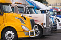 Modern yellow semi truck on foreground of other trucks with aluminum wheels and aluminum bumper guard the a number from different Stock Image
