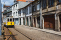Modern yellow and white trolley proceeds down narrow city street in Porto, Portugal Royalty Free Stock Image