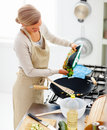 Modern young woman cooking food in the  kitchen Royalty Free Stock Images