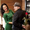 The modest young man with a rose and its girlfriend appointment in cafe fashionable men hat hands on Royalty Free Stock Photography