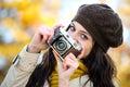 Modna kobieta bierze fotografię w jesieni z retro kamerą Obraz Royalty Free