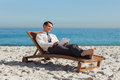 Młody biznesmen relaksuje na pokładu krześle używa jego pastylkę Zdjęcia Royalty Free